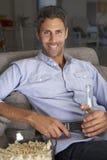 Hombre hispánico en Sofa Watching TV Foto de archivo libre de regalías