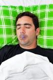 Hombre hispánico enfermo que pone en cama con un termómetro Imagenes de archivo