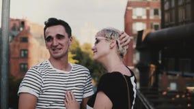 Hombre hispánico feliz de la cámara lenta y muchacha europea que hablan y que ríen junto en un puente grande de la ciudad en el v almacen de metraje de vídeo