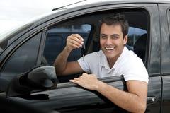 Hombre hispánico feliz en su nuevo coche imagen de archivo