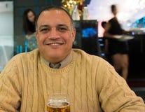 Hombre hispánico feliz en una cerveza de consumición del restaurante Imagen de archivo