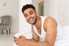 Hombre hispánico hermoso que miente en cama usando el teléfono elegante de la célula, Guy Happy Smile joven Fotografía de archivo