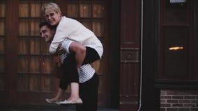 Hombre hispánico joven feliz de la cámara lenta que lleva a su novia en su risa trasera, disfrutando de la fecha romántica de la  almacen de video