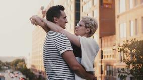 Hombre hispánico joven hermoso y mujer europea que se colocan y que abrazan en un puente de la puesta del sol de Nueva York que c almacen de metraje de vídeo