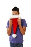 Hombre hispánico joven que oculta detrás de un sombrero de Santa Fotos de archivo libres de regalías