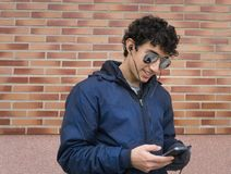 Hombre hispánico joven que se coloca en la calle que mira su teléfono celular Imagen de archivo libre de regalías