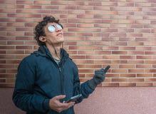 Hombre hispánico joven que se coloca en la calle que mira su teléfono celular Imagen de archivo