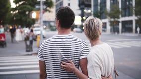 Hombre hispánico joven sonriente de la cámara lenta que abraza a su novia caucásica cerca de la travesía atmosférica de la calle  almacen de video