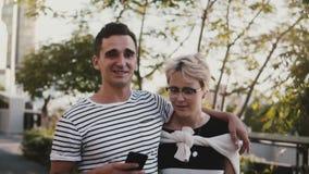 Hombre hispánico joven sonriente feliz de la cámara lenta y paseo europeo de la mujer que abrazan, usando smartphone en un día de almacen de metraje de vídeo