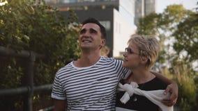 Hombre hispánico joven sonriente feliz de la cámara lenta y paseo europeo de la mujer que miran uno a en una calle de la ciudad d metrajes