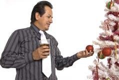 Hombre hispánico que mira un árbol de navidad adornado Imágenes de archivo libres de regalías