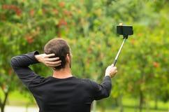 Hombre hispánico que presenta con el palillo del selfie en parque Imágenes de archivo libres de regalías