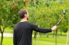 Hombre hispánico que presenta con el palillo del selfie en parque Foto de archivo libre de regalías