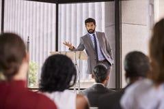 Hombre hispánico que presenta el seminario del negocio que se inclina en el atril Fotografía de archivo