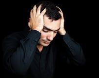 Hombre hispánico que sufre un dolor de cabeza fuerte Imagen de archivo