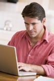 Hombre hispánico que usa la computadora portátil en el país Foto de archivo