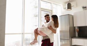 Hombre hispánico sonriente feliz Carry Asian Woman, par romántico joven junto en cocina almacen de video