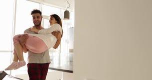 Hombre hispánico sonriente feliz Carry Asian Woman, par romántico joven que da vuelta a Aroud junto en cocina almacen de metraje de vídeo