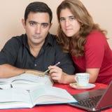 Hombre hispánico y mujer que estudian en casa Fotografía de archivo libre de regalías