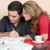 Hombre hispánico y mujer que estudian en casa Imagen de archivo libre de regalías