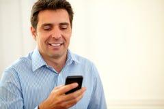 Hombre hispánico que manda un SMS con su teléfono móvil Imagenes de archivo