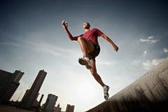Hombre hispánico que se ejecuta y que salta de una pared Foto de archivo libre de regalías
