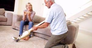 Hombre hoovering la alfombra mientras que el socio se relaja Imagen de archivo