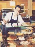 Hombre hospitalario con las tartas de crema deliciosas Imagenes de archivo