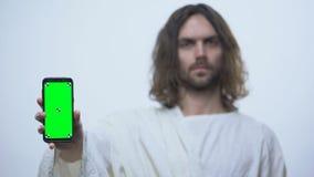 Hombre igualmente Jesús que sostiene el smartphone pre cerrado, uso móvil de la biblia, en línea metrajes