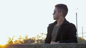Hombre impaciente joven en la capa que espera alguien en café en la ciudad metrajes