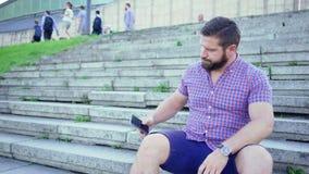 Hombre impaciente joven que se sienta en las escaleras que esperan alguien, tiro del resbalador almacen de video