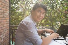 Hombre independiente asiático joven que trabaja en el ordenador portátil foto de archivo libre de regalías