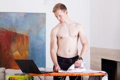 Hombre independiente durante planchar Imagenes de archivo