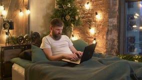 Hombre independiente que miente en la cama que trabaja con el ordenador portátil almacen de metraje de vídeo
