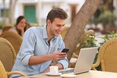 Hombre independiente que trabaja con un ordenador portátil y un teléfono en un restaurante Imagen de archivo libre de regalías