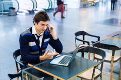 Hombre independiente que usa la PC del teléfono móvil y del ordenador portátil Imagenes de archivo