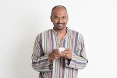 Hombre indio casual maduro que usa apps móviles Imagenes de archivo