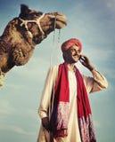 Hombre indio en el concepto de la comunicación del camello del teléfono fotos de archivo