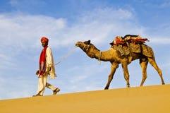 Hombre indio indígena que camina a través del desierto con su camello Foto de archivo libre de regalías