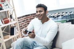 Hombre indio joven fascinado por el juego en la consola imagenes de archivo