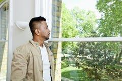 Hombre indio joven que mira hacia fuera la ventana Fotografía de archivo libre de regalías