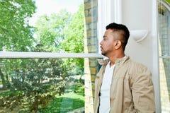 Hombre indio joven que mira hacia fuera la ventana Fotos de archivo