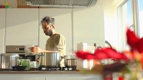 Hombre indio joven que prepara el almuerzo en la cocina almacen de video