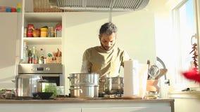 Hombre indio joven que prepara el almuerzo en la cocina almacen de metraje de vídeo