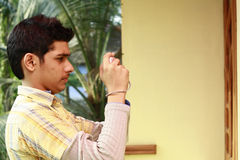 Hombre indio joven que toma la foto en cámaras digitales Fotografía de archivo libre de regalías