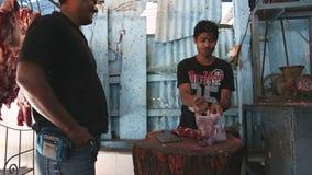 Hombre indio que clasifica y que taja la carne en la carnicería en Bombay almacen de metraje de vídeo
