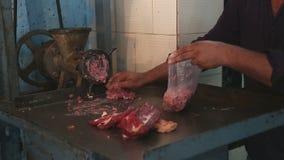 Hombre indio que pica y que clasifica la carne en la carnicería en Bombay almacen de metraje de vídeo