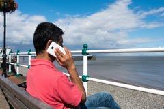 Hombre indio que se sienta en el banco que habla en Smartphone Foto de archivo
