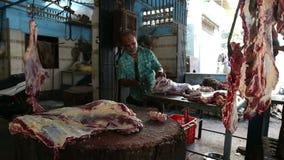 Hombre indio que taja la carne en la carnicería en Bombay metrajes