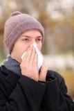 Hombre infectado que sopla su nariz en papel de tejido Imagen de archivo libre de regalías